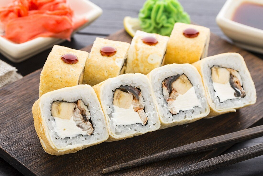 Sushi rolls with smoked eel and banana on a wooden board
