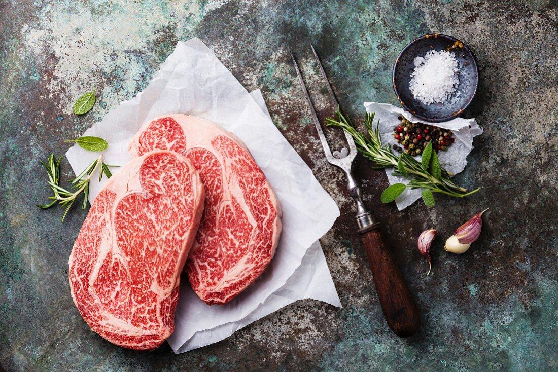 Raw fresh marbled meat Black Angus Steak Ribeye, seasonings and meat fork on metal background
