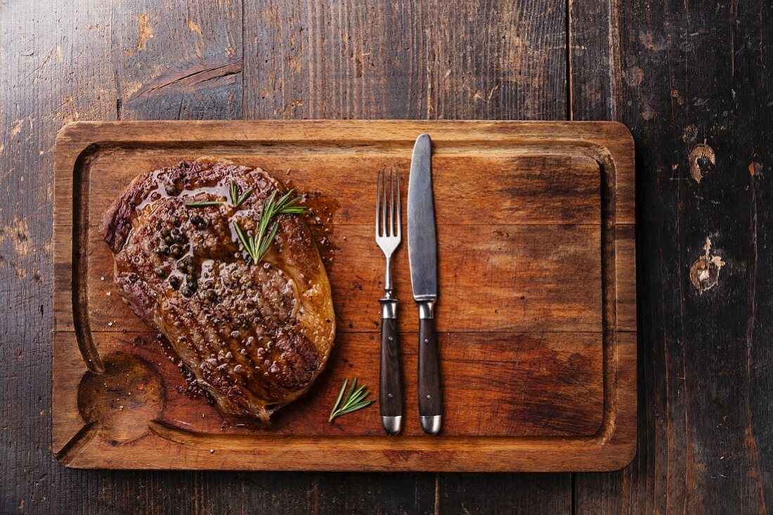 Grilled Black Angus Steak Ribeye and fork and knife on meat cutting board on dark wooden background