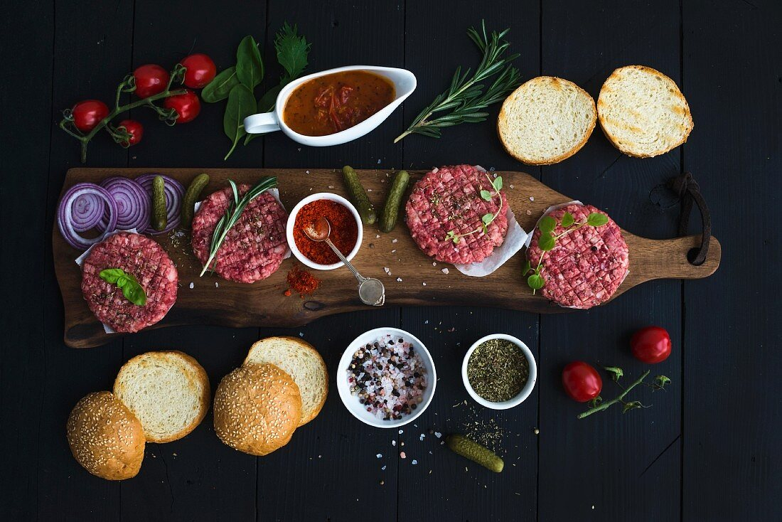 Ingredients for cooking burgers: Raw ground beef meat, red onion, cherry tomatoes, pickles, tomato sauce, cheese, buns