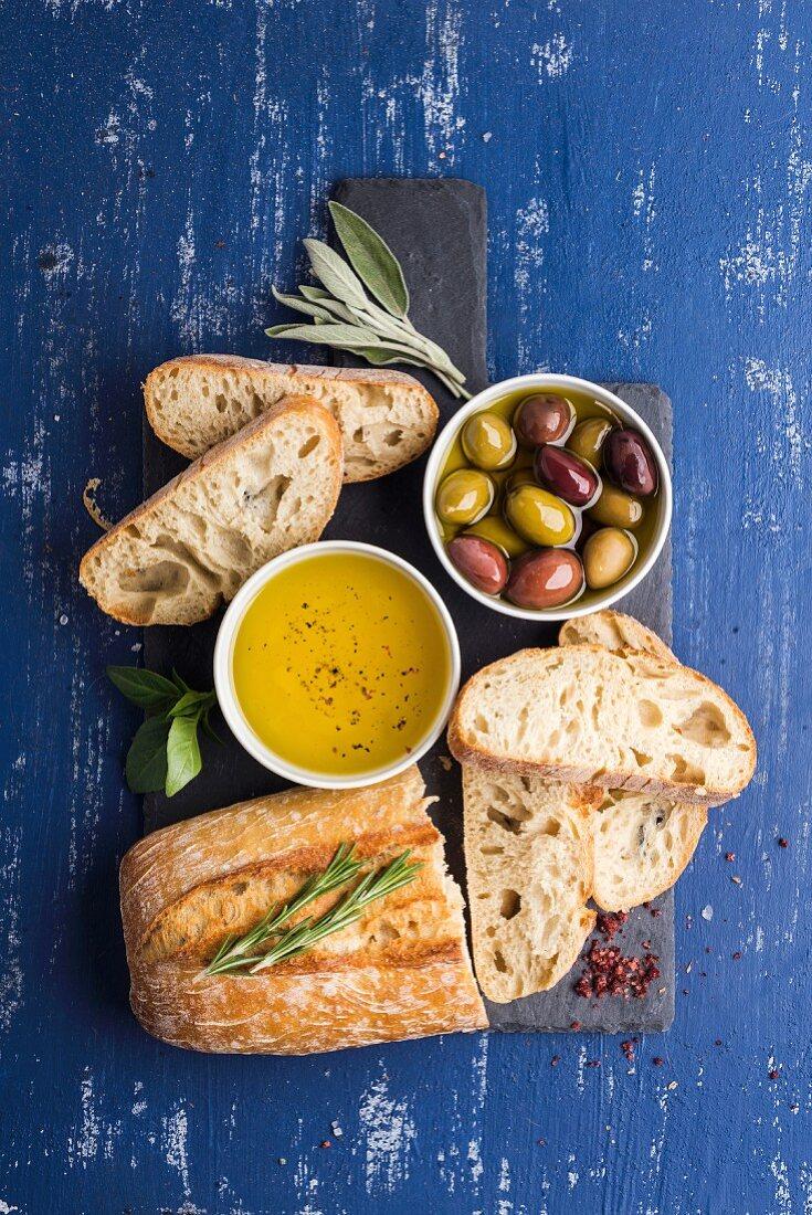 Mediterranean snacks set: Olives, oil, herbs and sliced ciabatta bread on black slate stone board