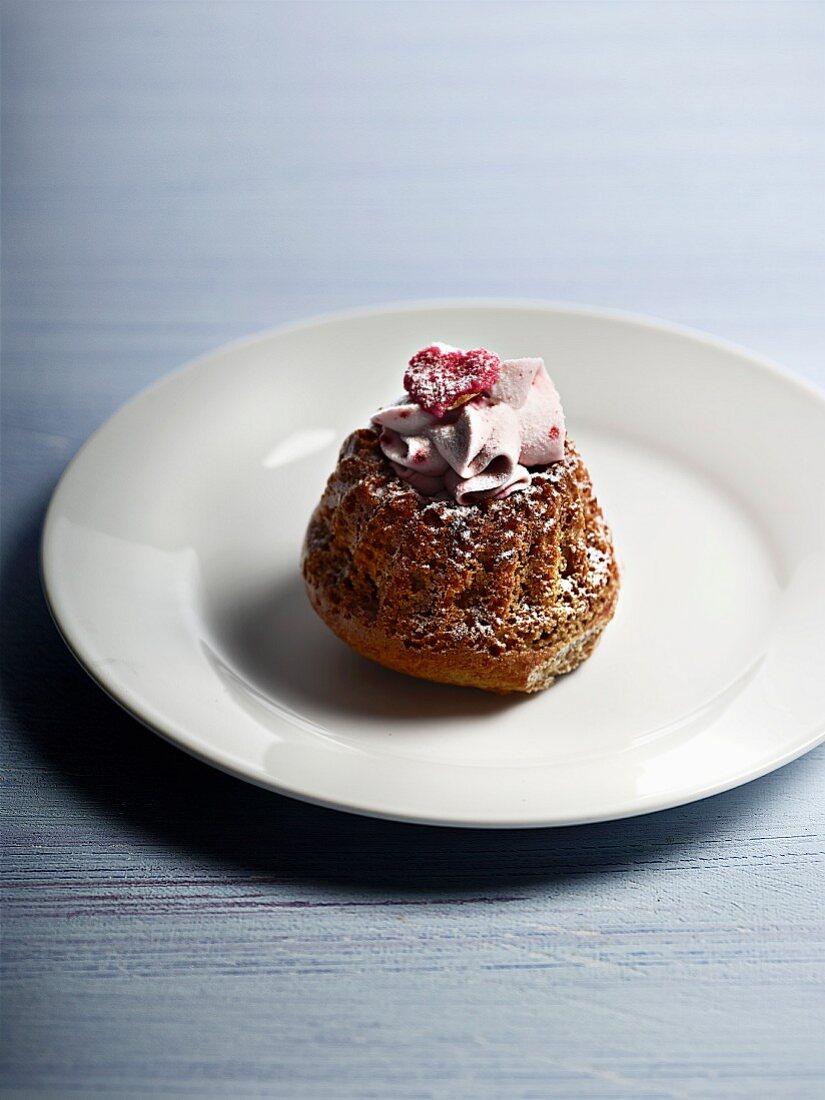 Mini gugelhupf with icing sugar, cream and raspberries