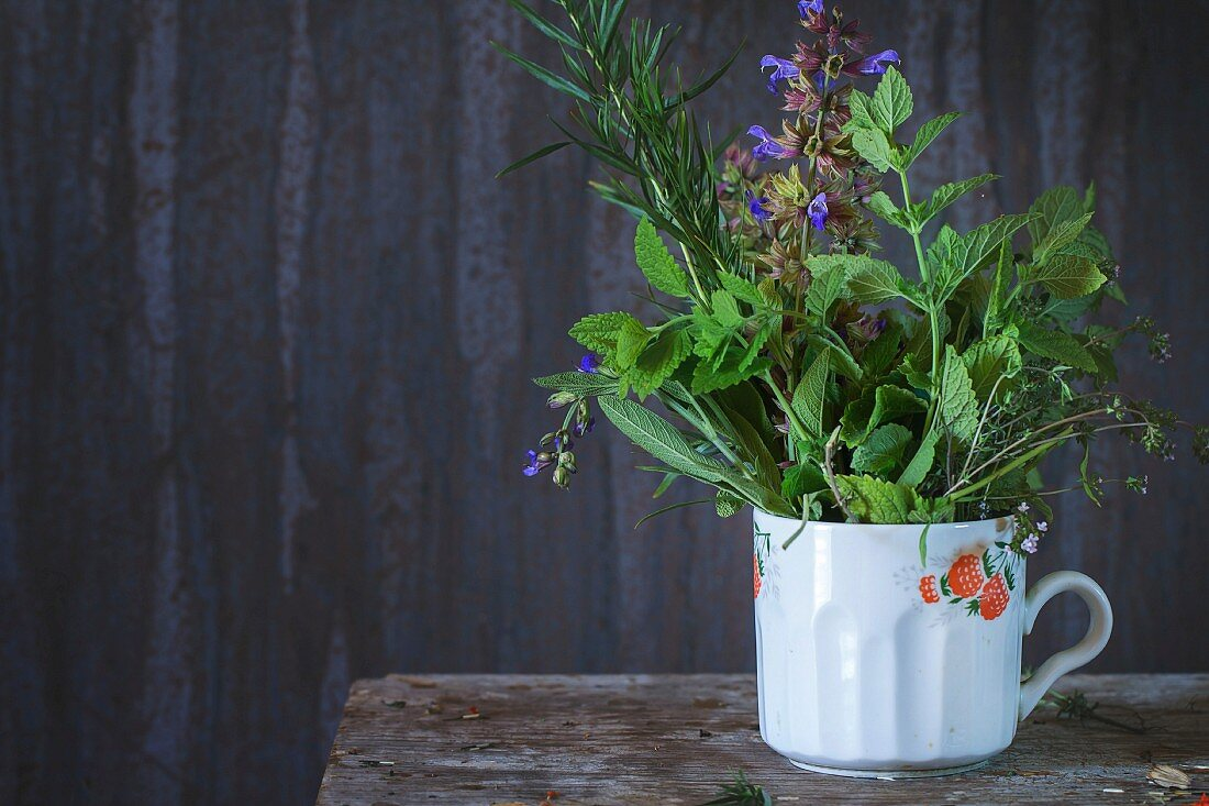 Old cup with assortment of fresh herbs mint, oregano, thym, blooming sage over old wooden background