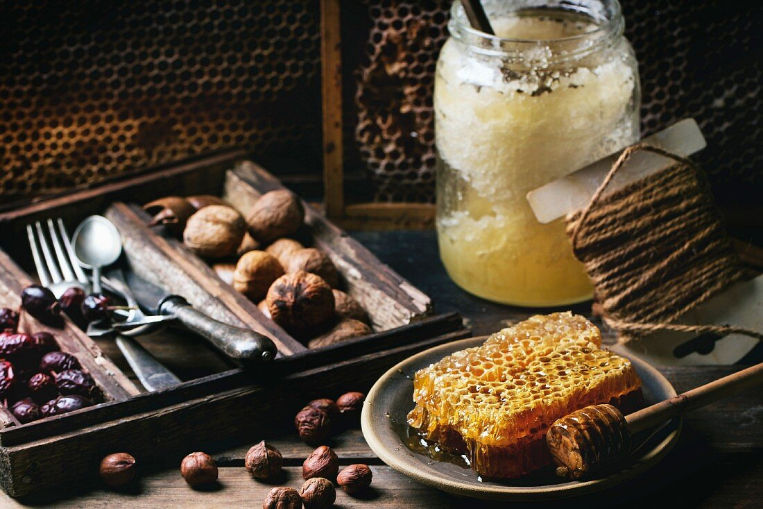 Fresh honeycomb with jar of old honey and mix of nuts over old wooden table