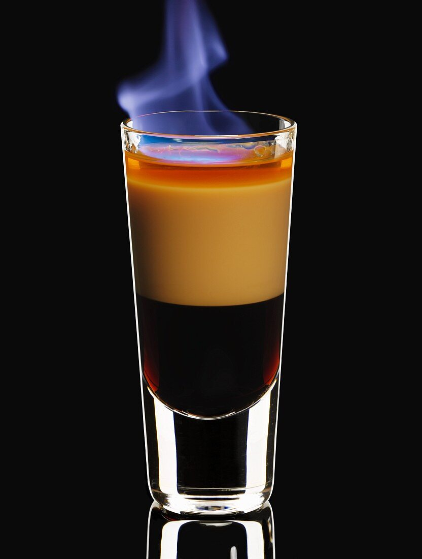 A flambéed B-52 cocktail in a glass on a black background