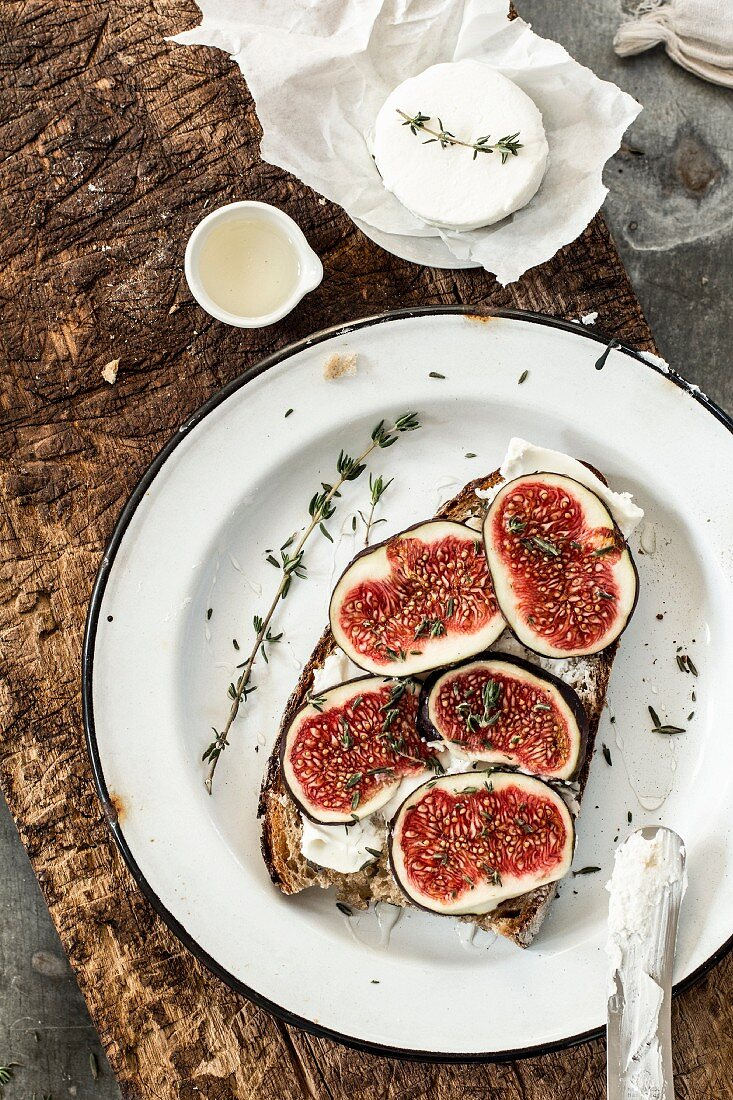 Fig halves on bread with goat's cheese, honey and thyme