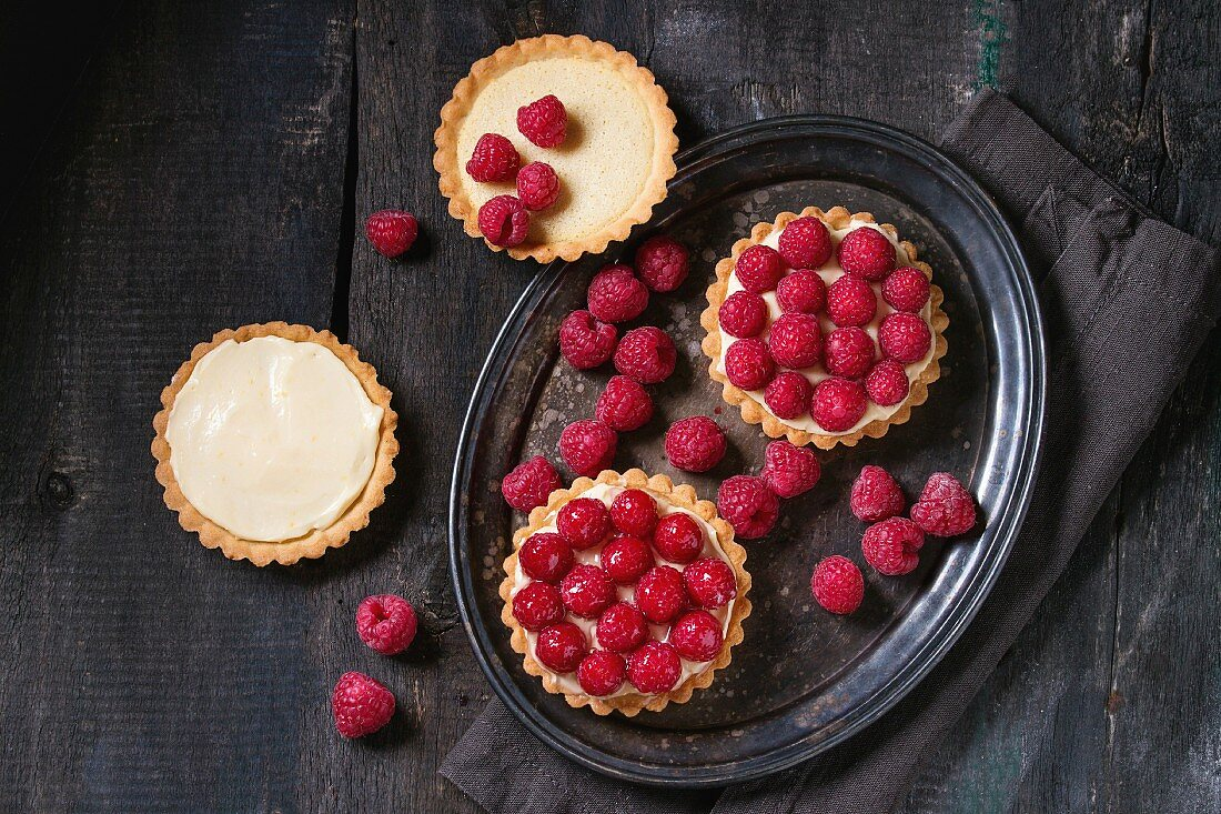 Unfinished and ready to eat tartlets with custard and fresh ripe raspberries
