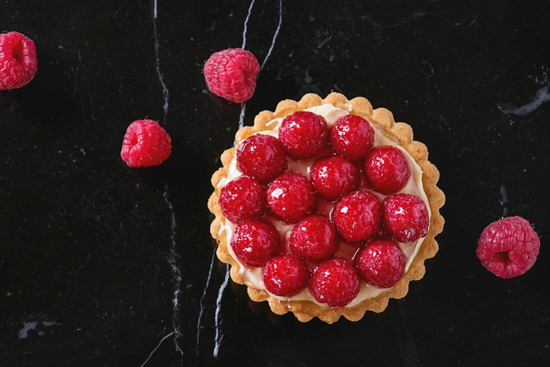 Tartlet with custard and fresh glazed raspberries, served on black marble surface