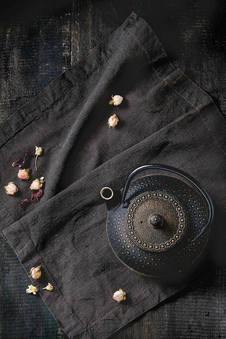 Black iron asian style teapot with dry tea roses on black textile napkin