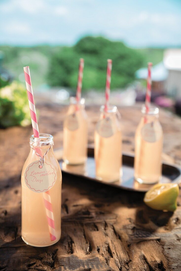 Lemon Melon Drop cocktail in bottles with pink-striped straws