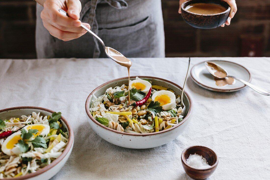 Knuspriges Gemüse mit gekochtem Ei wird mit warmer Erdnusssauce beträufelt