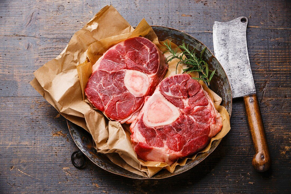 Raw fresh cross cut veal shank for making Osso Buco on metal copper plate on wooden background with meat cleaver