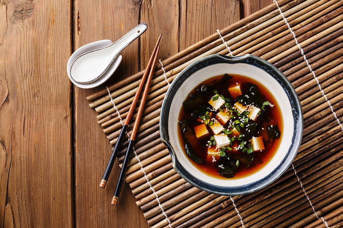 Miso Soup with tofu, seaweed and sesame in bowl on wooden background