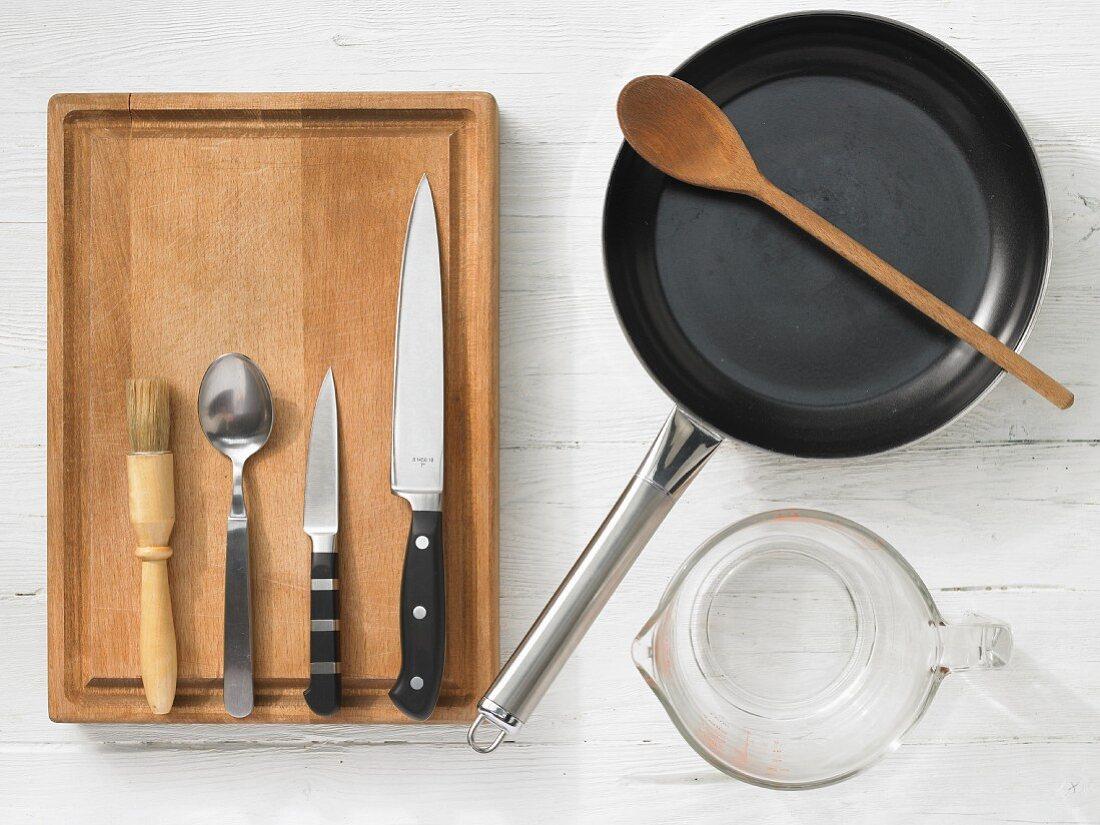 Kitchen utensils: pan, measuring cup, brush, spoon, knives