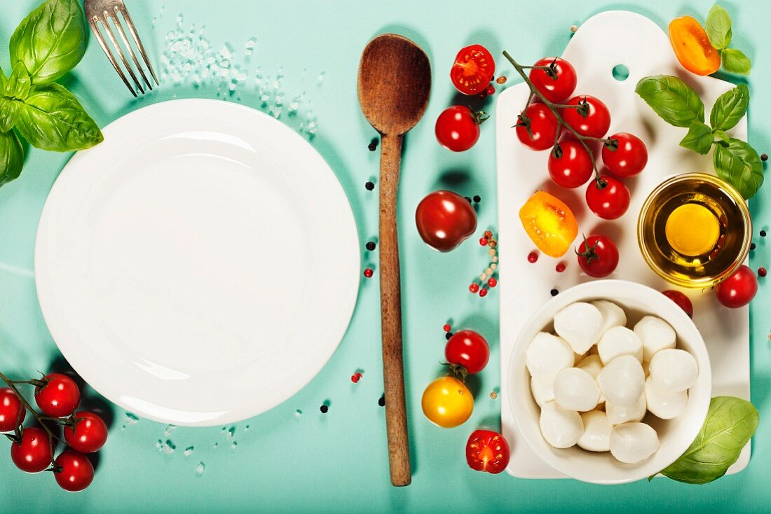 White ceramic serving board and caprese salad ingredients over light blue background