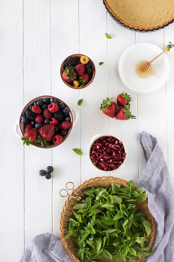Ingredients for summer berry tart displayed on a white wood board