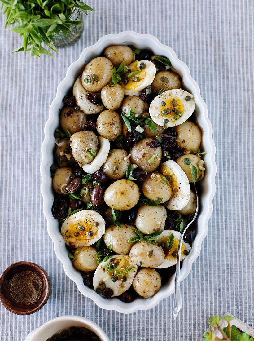 Baby Potatoes with Sun-Dried Tomatoes and Caper Dressing displayed in a large oval bowl