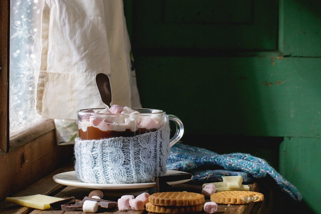 Glass cup of Hot chocolate with marshmallows in knitted cup holder with cookies, chopping chocolate and mittens