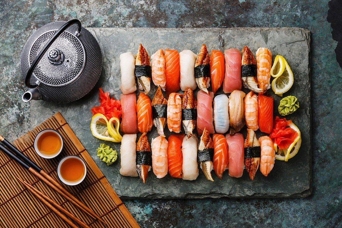 Sushi Set nigiri with tea served on gray stone slate on metal background