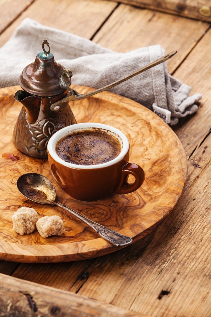 Cup of black coffee and Turkish Cezve on wooden background