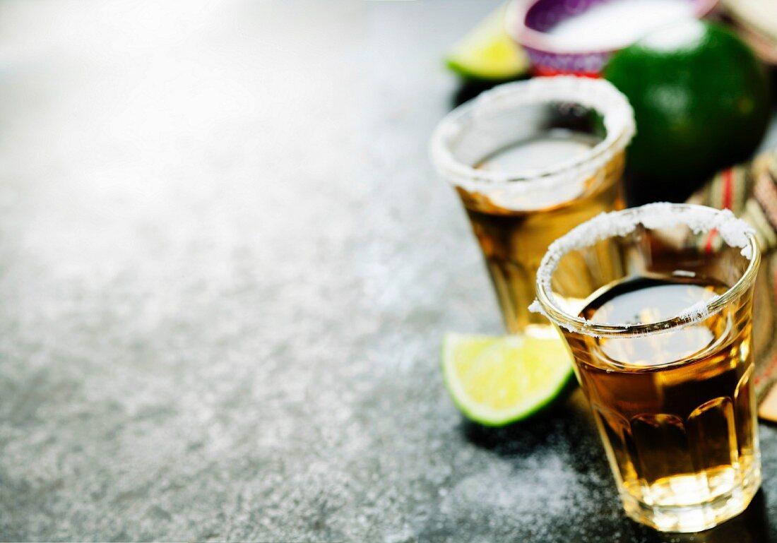 Tequila mit Limette und Salzrand vor rustikalem Hintergrund