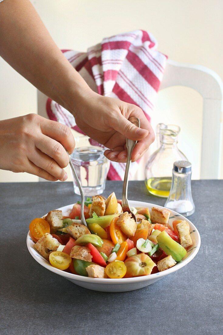 Frauenhände mischen Zutaten für Panzanella-Salat