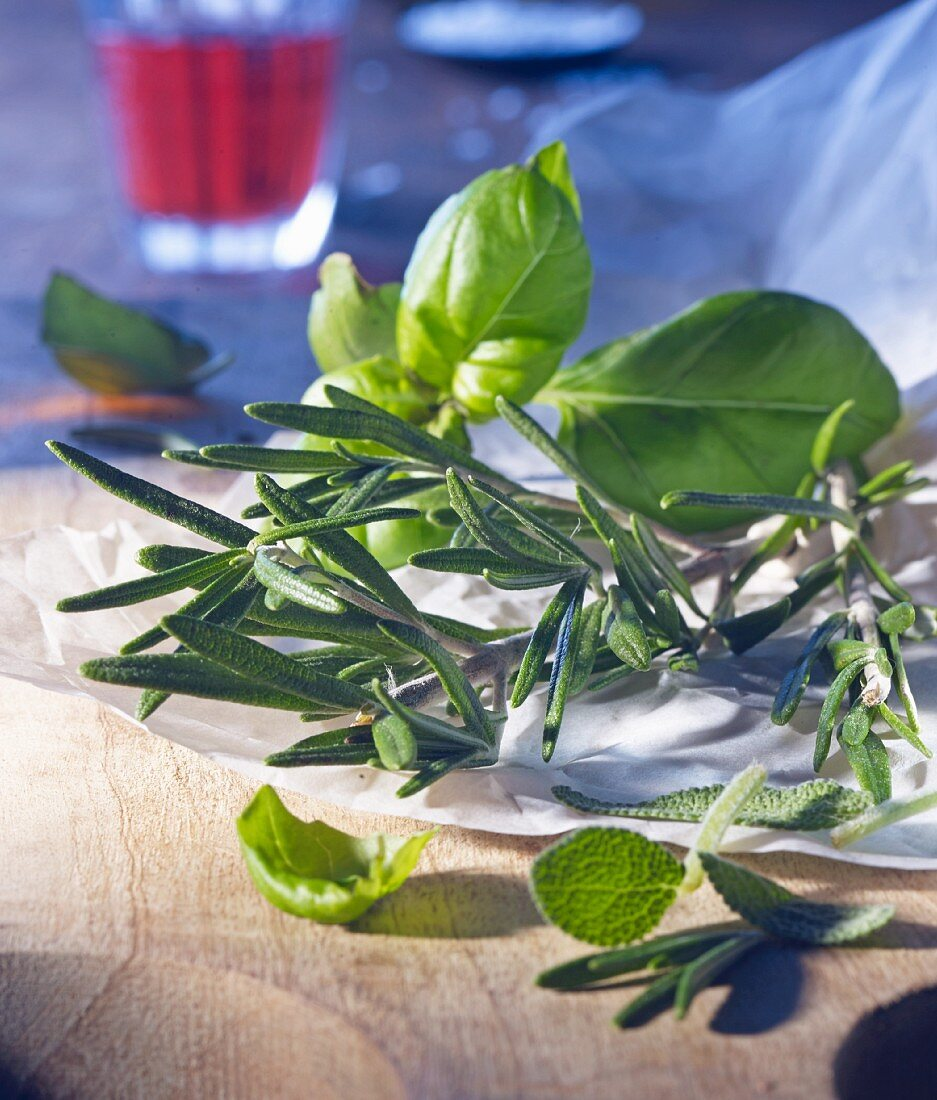 Fresh herbs (basil, rosemary and sage) on paper