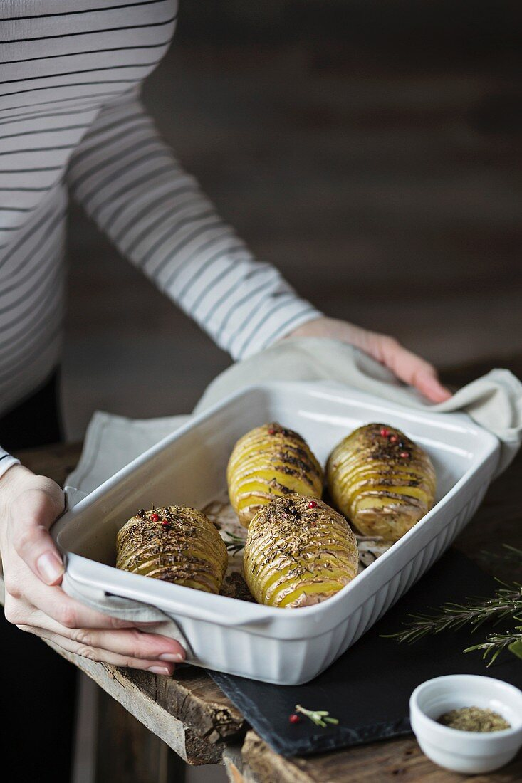 Woman with roasted hasselback potatoes