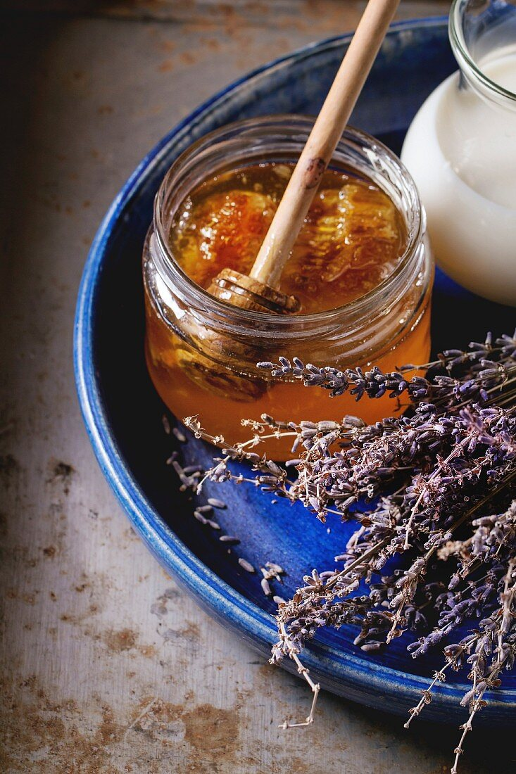 Open glass jar of liquid honey with honeycomb and honey dipper inside, milk and dry lavender