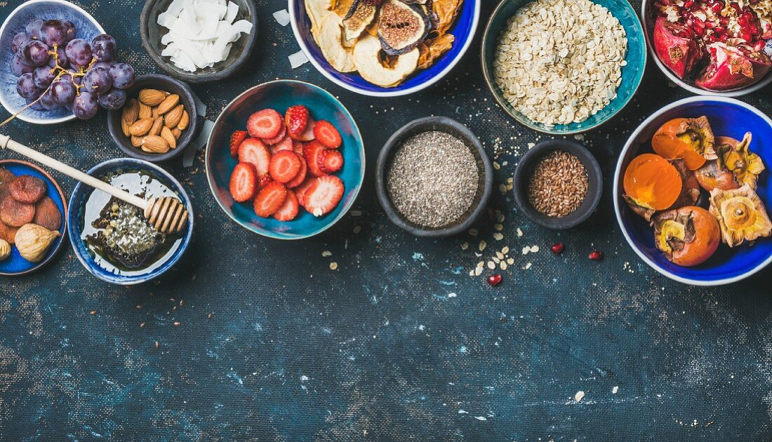 Ingredients for healthy breakfast: Fresh and dried fruit, chia seeds, oatmeal, nuts, honey