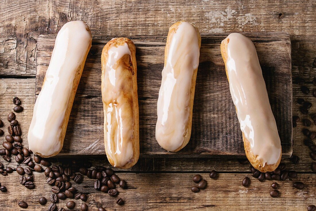 Fresh homemade Coffee eclairs with different glaze and coffee beans on wood chopping board
