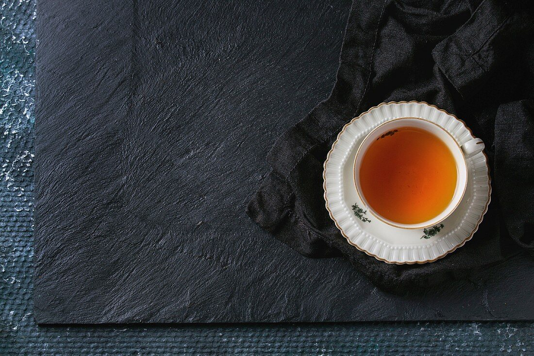 White vintage cup of hot tea on saucer standing on black textile napkin over black slate texture background