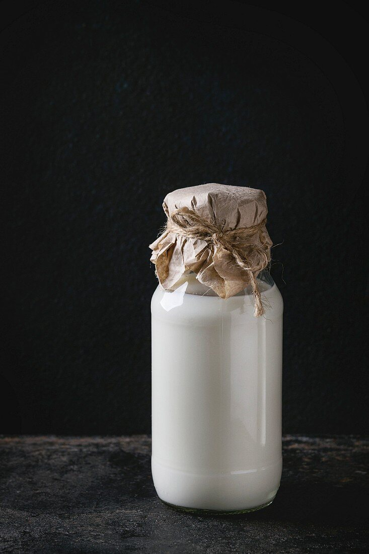 Glass bottle full of milk closed by paper and thread over black background