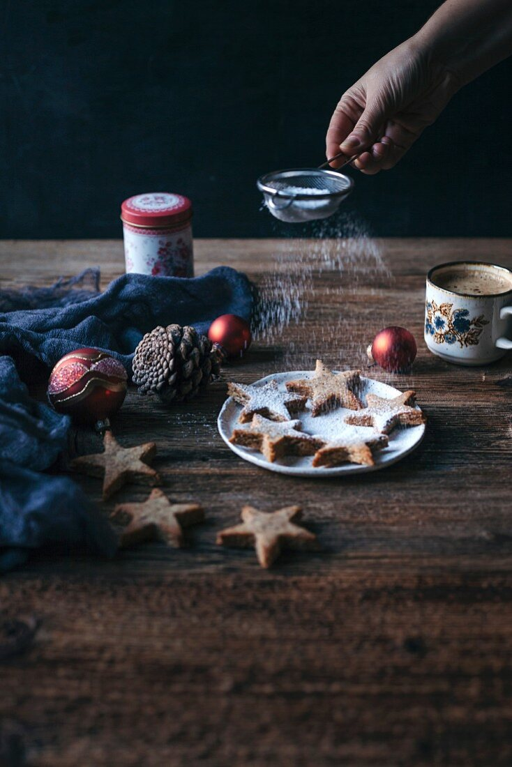 Woman dusting almonds cinnamon Christmas cookies with powdered sugar on a plate and rustic wooden table