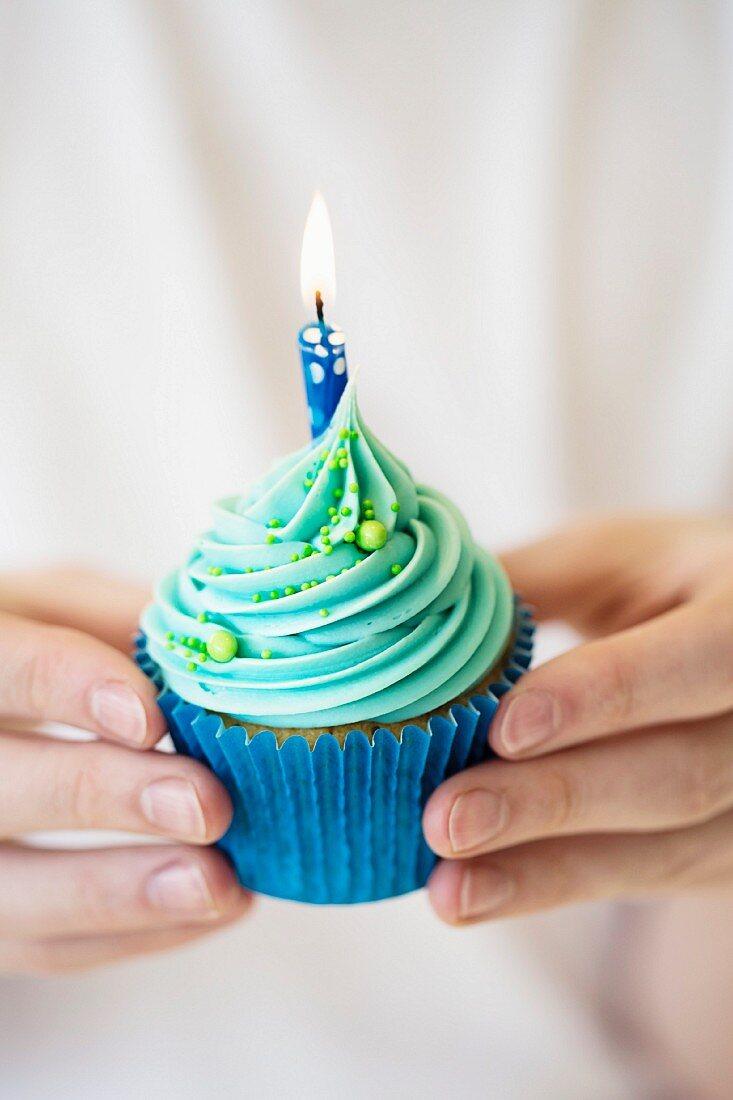 Hände halten Geburtstags-Cupcake mit brennender Kerze