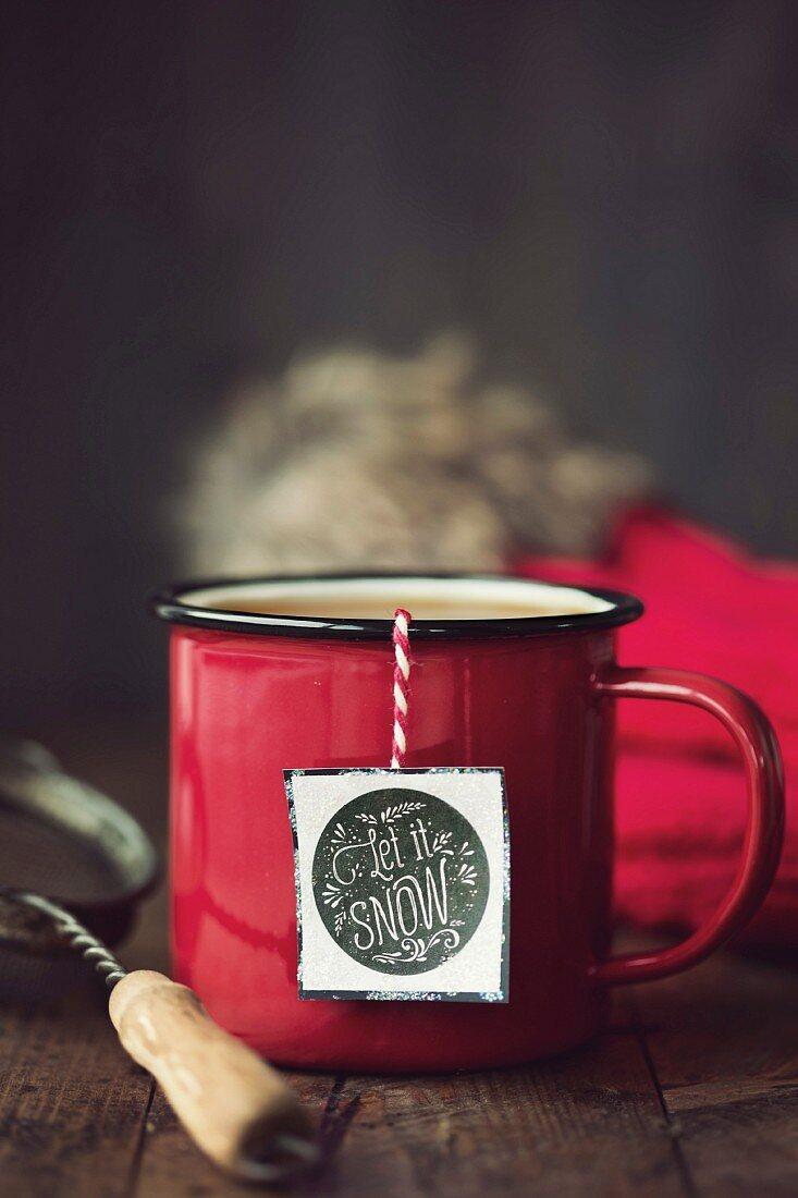 Enamel mug with festive tea bag tag