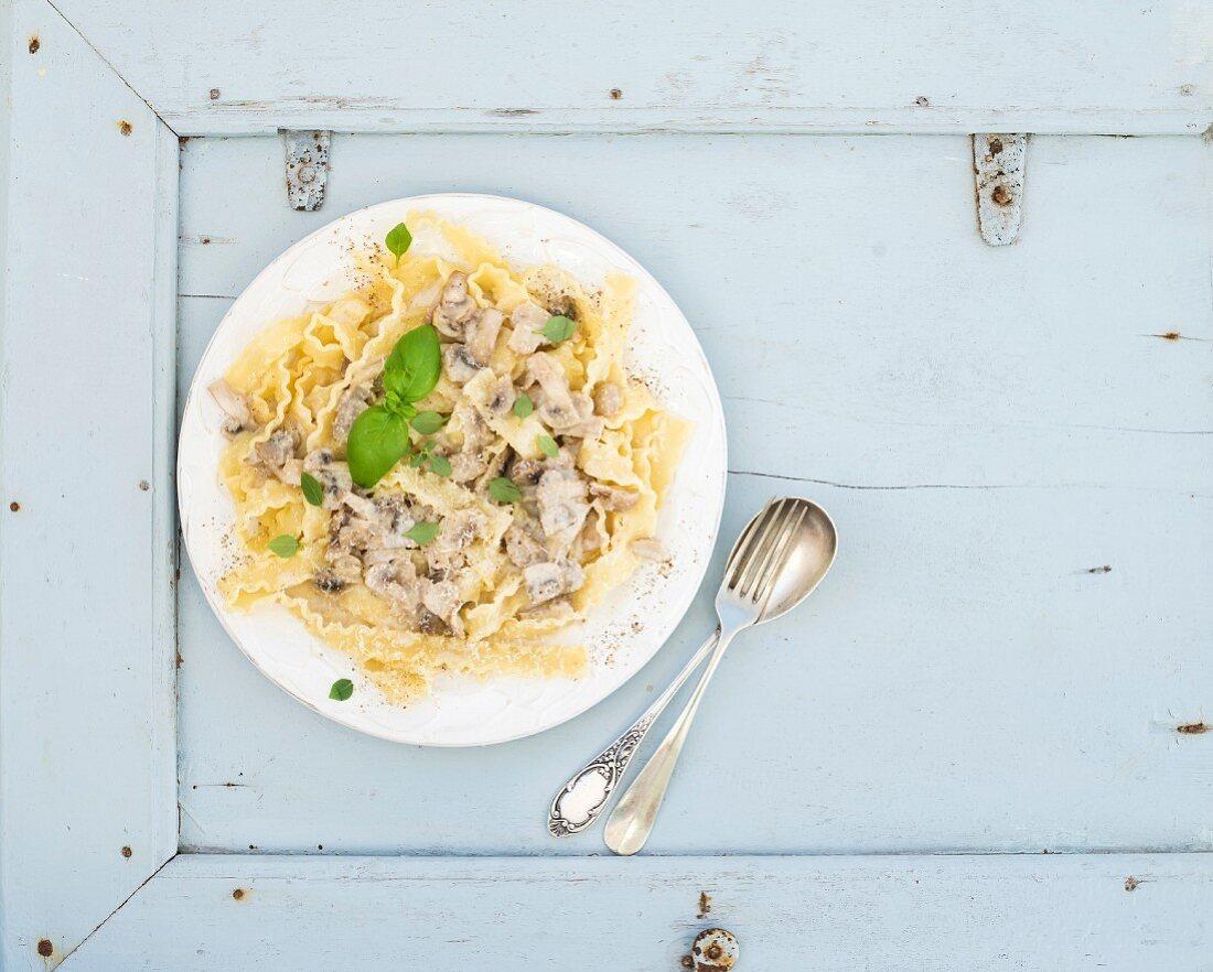 Pasta mafaldine with mushrooms and cream sauce in white ceramic plate over light blue wooden background