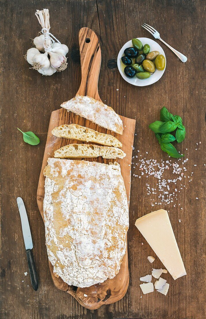 Freshly baked ciabatta bread with garlic, mediterranean olives, basil and Parmesan cheese on serving board