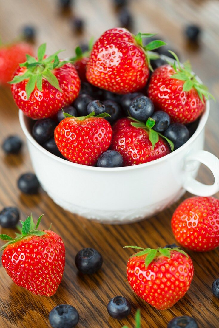 Bowl of strawberries and blueberries on a wooden table
