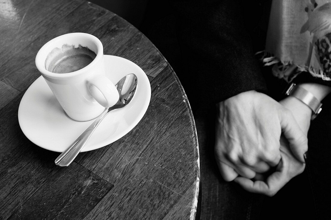 Hands drinking an espresso coffe in a Parisian cafe
