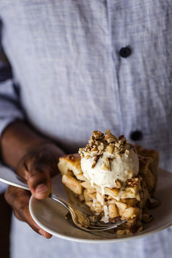 A man is holding a slice of a caramel pie topped with vanilla ice cream and chopped walnuts