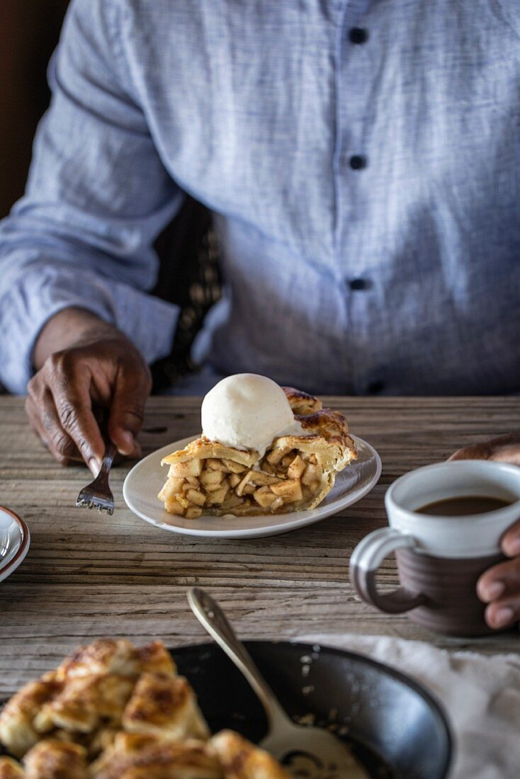 A man is served a slice of caramel apple pie topped with a scoop of vanilla bean ice cream
