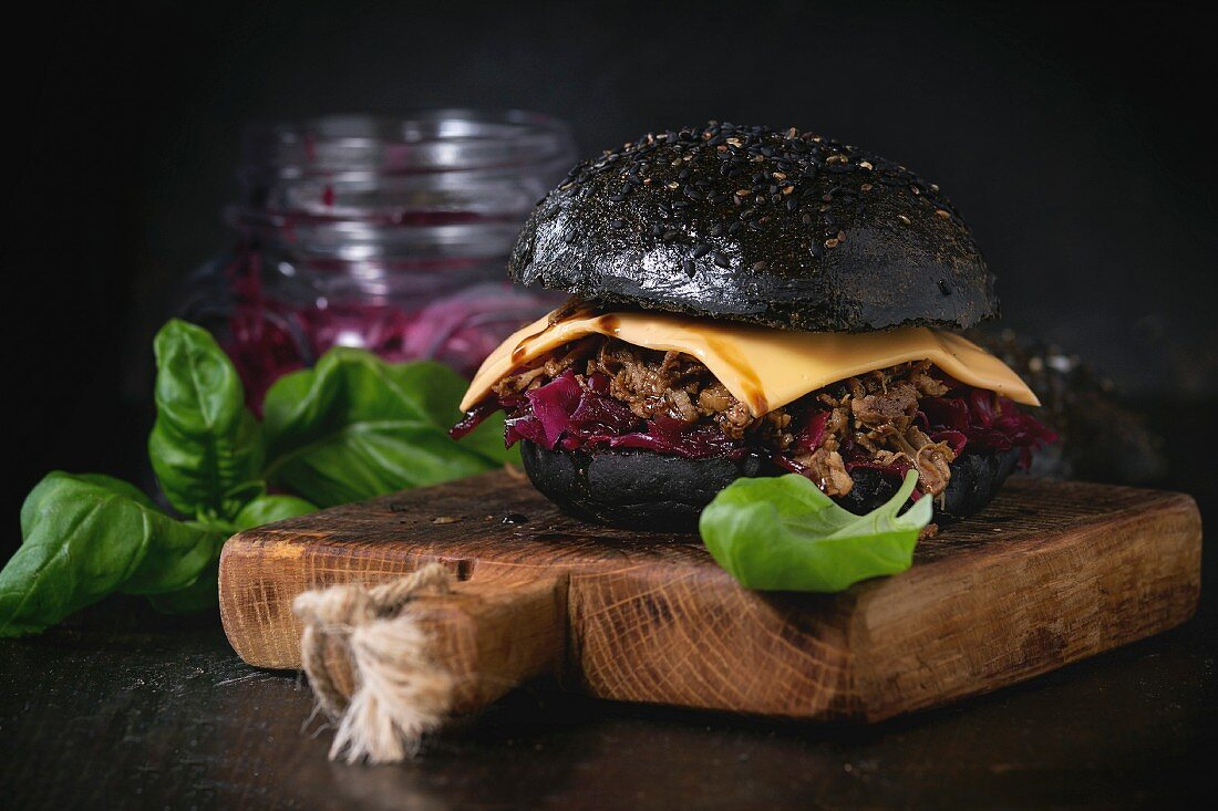 Black burger with stews, cheese, red cabbage and balsamic sauce served on wooden chopping board with fresh basil