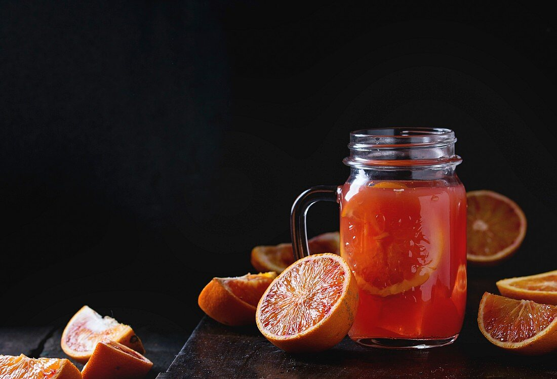 Sliced Sicilian Blood oranges and glass mason jar of fresh red orange juice over old wooden table
