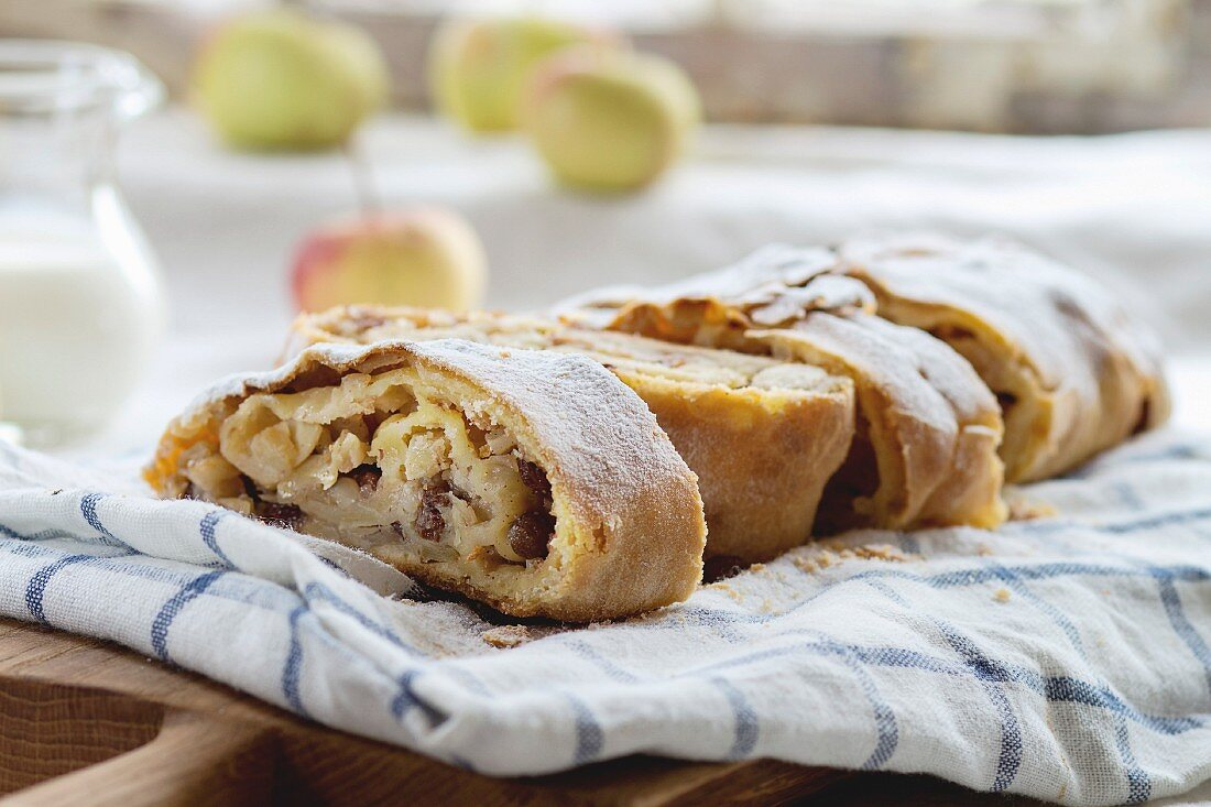 Sliced fresh baked homemade apple strudel over towel on kitchen table with jug of milk and apples