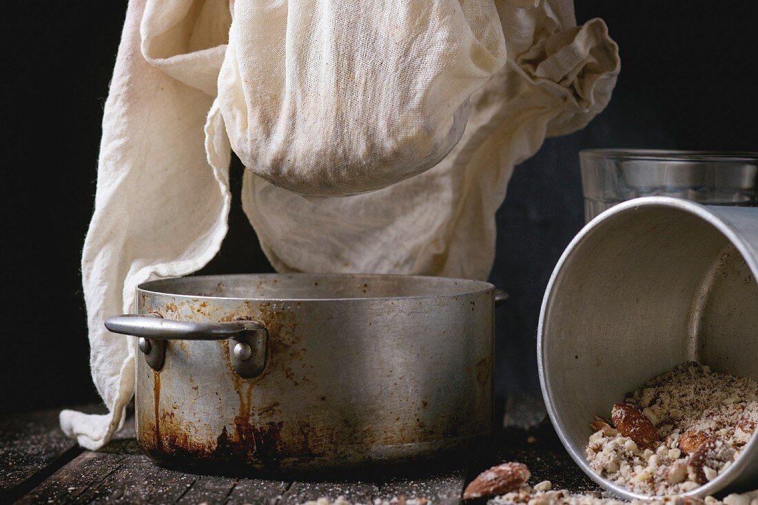 Process of making non-dairy almond milk - extraction of grain almond via white textile at vintage pan