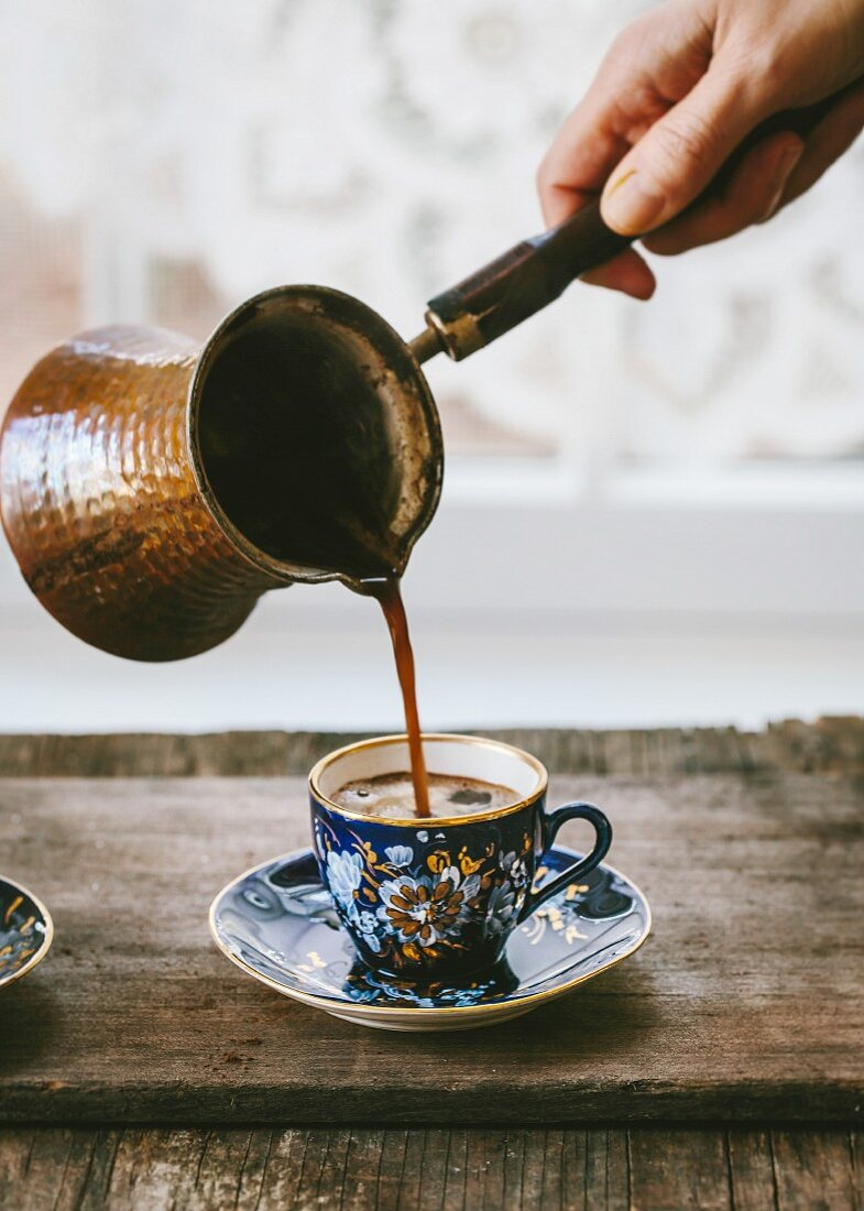 A woman is pouring Turkish Coffee in to a vintage Turkish coffee cup