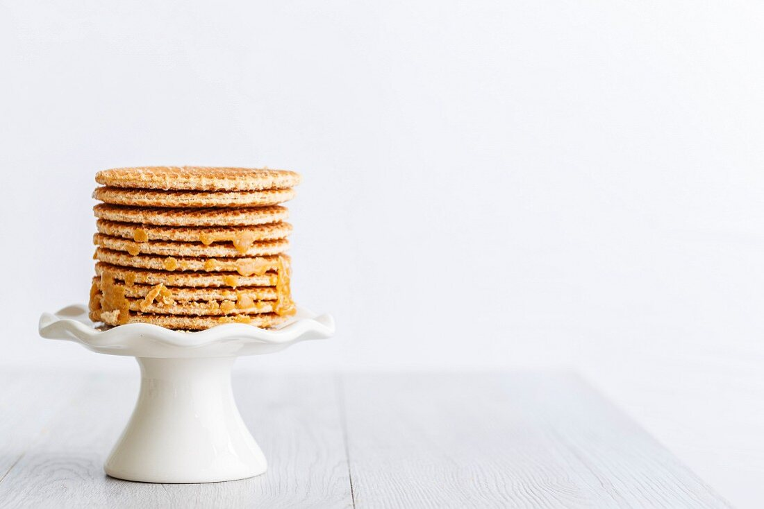 Stack of Dutch caramel waffles on a white stand