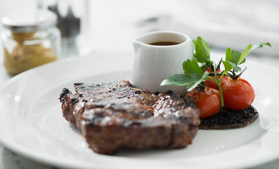 Steak and cherry tomatoes served on a white plate