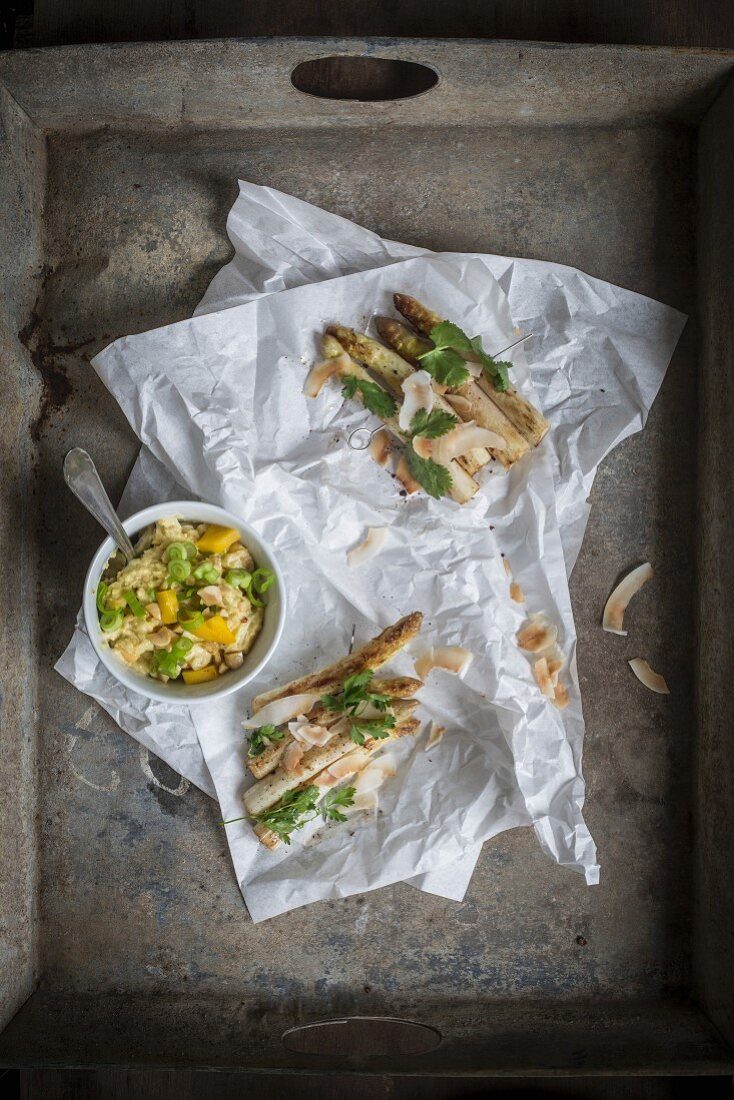 Asparagus satay and peanut dip served on sandwich paper and grey vintage tray